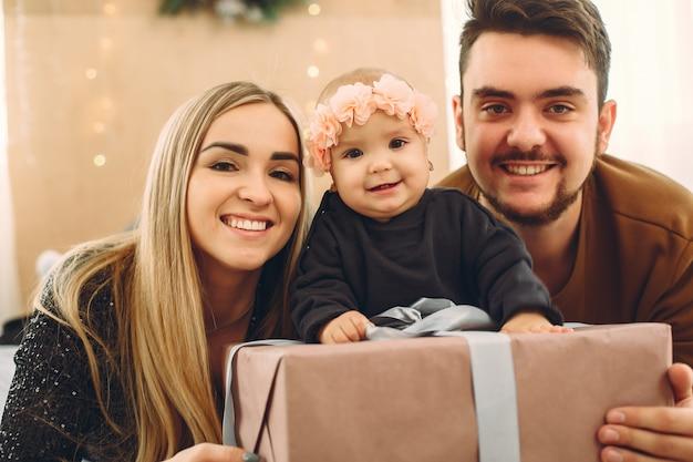 Família sentada em casa em uma cama com presentes Foto gratuita