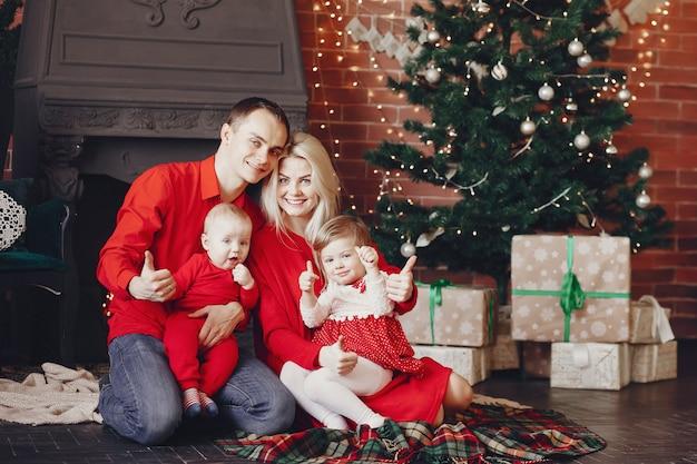 Família sentada em casa perto de árvore de natal Foto gratuita