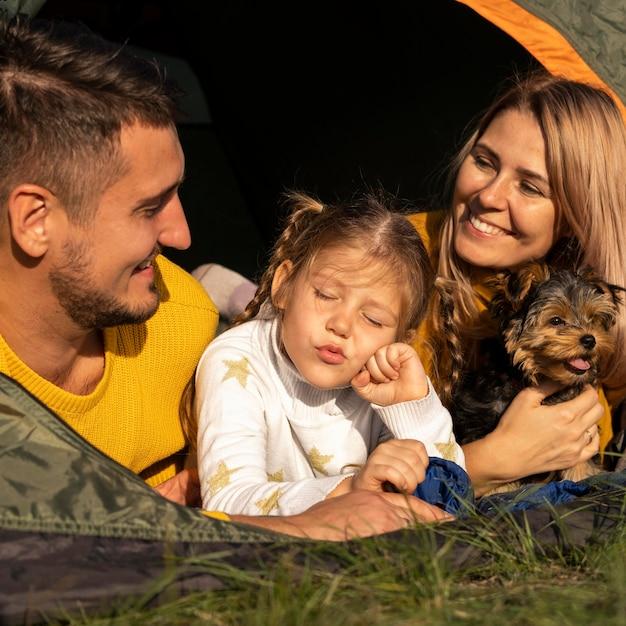 Família sentada em uma barraca com seu cachorro em close-up Foto gratuita