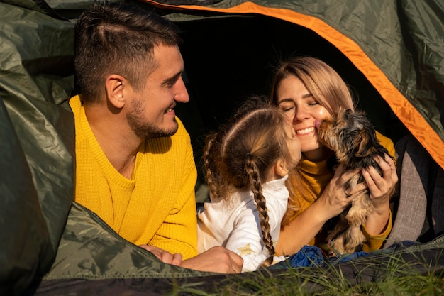 Família sentada em uma barraca com seu cachorro Foto gratuita