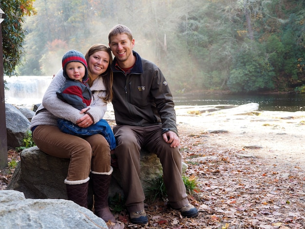 Família sentada em uma rocha cercada por uma cachoeira e vegetação sob o sol Foto gratuita