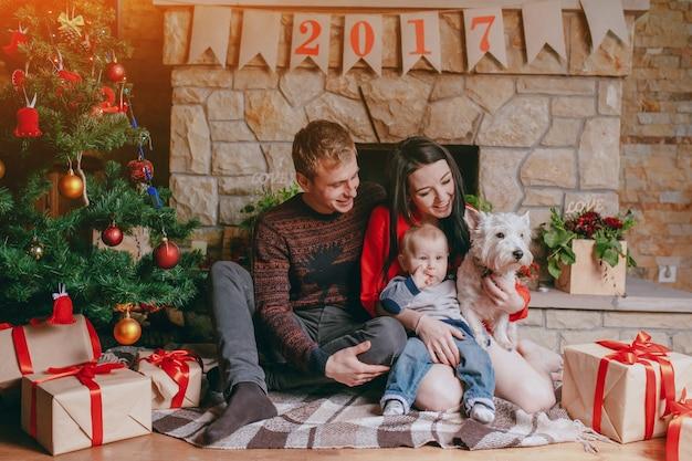 Família sentado em frente da lareira com seu bebê e seu cão e uma árvore de natal Foto gratuita