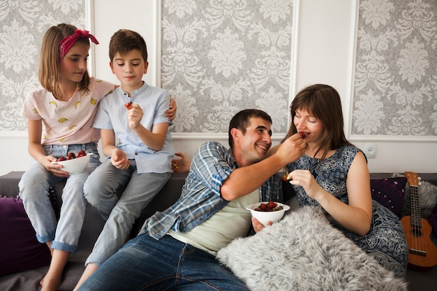 Família, sentar sofá, desfrutando, moranguinho, casa Foto gratuita