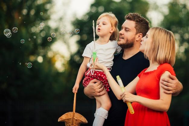 Família soprando bolhas de sabão ao ar livre Foto gratuita
