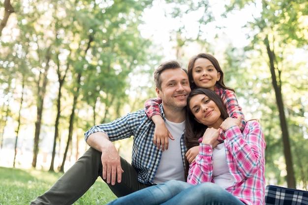 Família sorridente a passar tempo juntos no parque Foto gratuita