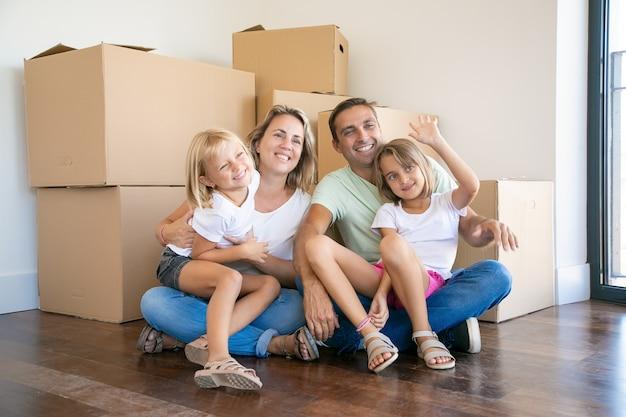 Família sorridente com crianças sentadas no chão perto de caixas de papelão e relaxando Foto gratuita