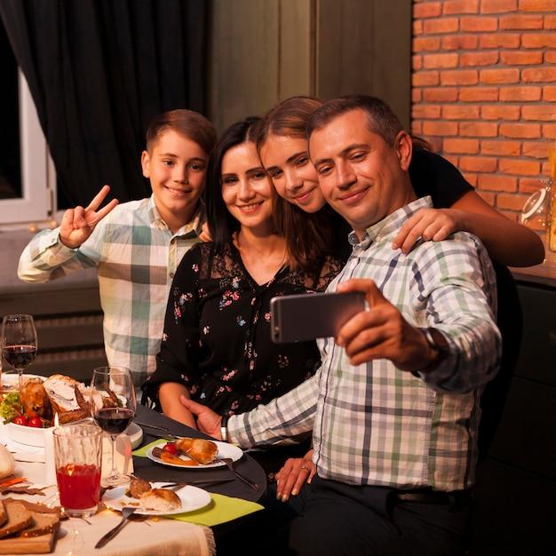 Família sorridente com foto média tirando selfie Foto gratuita