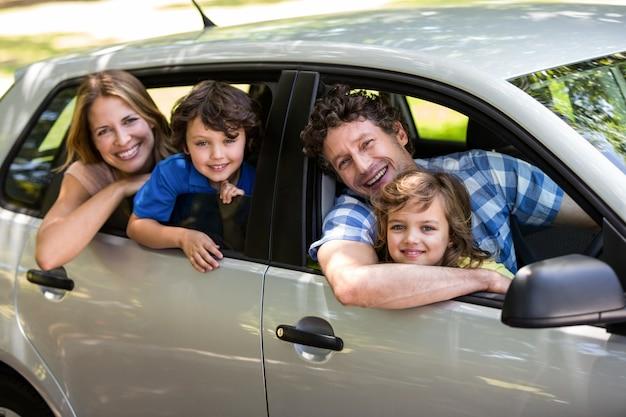 Família sorridente, sentado no carro Foto Premium
