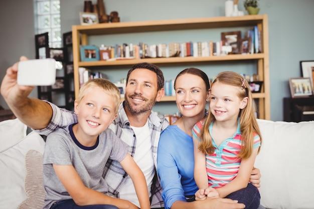 Família tomando selfie com telefone celular no sofá em casa Foto Premium