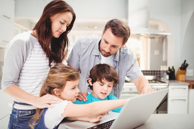 Família usando laptop na mesa Foto Premium