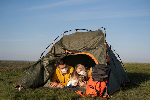 Família usando máscaras e sentada em uma barraca com seu cachorro Foto gratuita