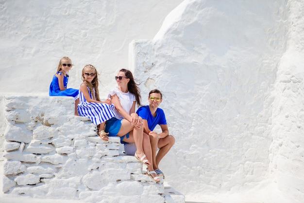 Família vacayion na europa. pais e filhos na rua da aldeia tradicional grega típica com paredes brancas e portas coloridas na ilha de mykonos, na grécia Foto Premium