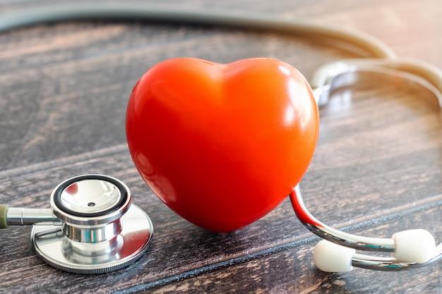 Família vermelha de coração, estetoscópio e ícone na mesa de madeira. conceito de seguro médico Foto Premium