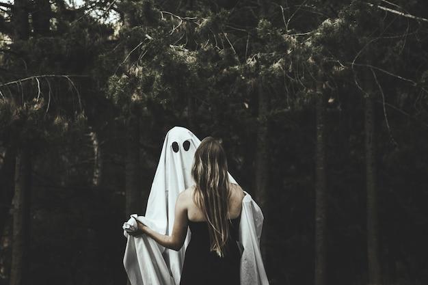 Fantasma e dama abraçando no parque Foto gratuita