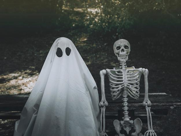 Fantasma e esqueleto sentado no banco no parque Foto gratuita