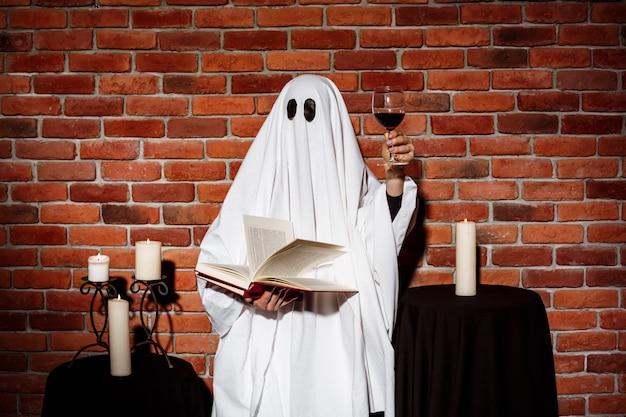 Fantasma, segurando o livro e o vinho sobre a parede de tijolos. festa de halloween. Foto gratuita