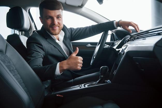 Fantástico. empresário moderno experimentando seu novo carro no salão automotivo Foto gratuita