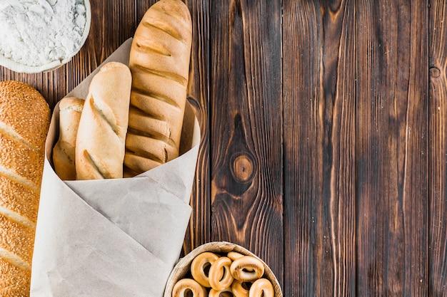 Farinha, baguetes e bagels no fundo de madeira Foto gratuita