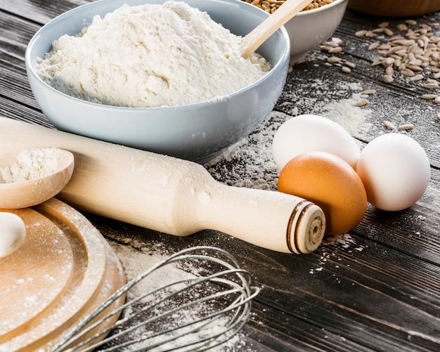 Farinha branca com ovos na mesa da cozinha Foto gratuita