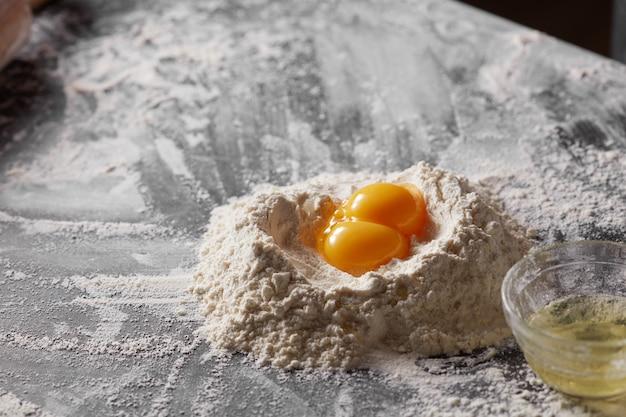 Farinha branca e gema em uma mesa de cozinha escura Foto Premium