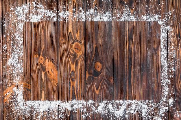 Farinha branca sobre a borda da moldura retangular na mesa de madeira Foto gratuita