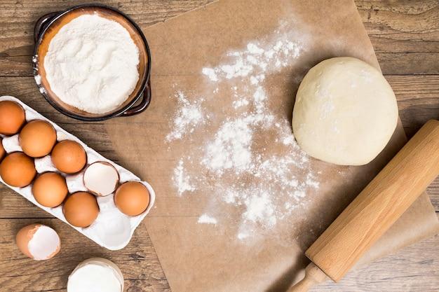 Farinha; caixa de ovos; massa; rolo em papel pergaminho sobre a mesa de madeira Foto gratuita