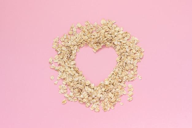 Farinha de aveia em forma de coração com espaço vazio para texto em fundo rosa. conceito de dieta Foto Premium