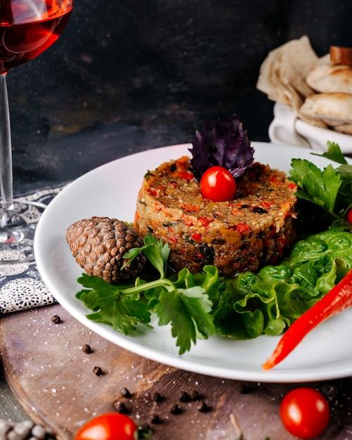 Farinha de carne, juntamente com salada verde e tomate cereja vermelho dentro de chapa branca na superfície cinza Foto gratuita