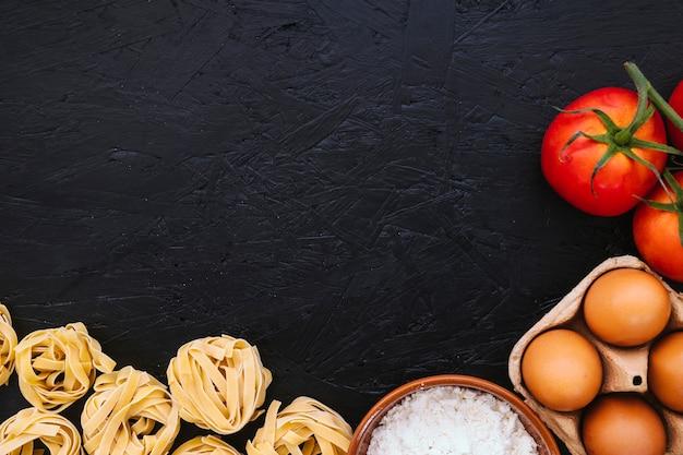 Farinha e ovos perto de macarrão e tomate Foto gratuita