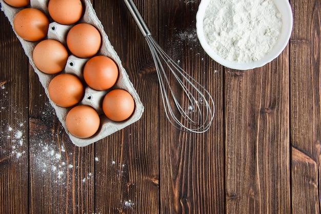 Farinha em uma tigela com ovos, bata plana coloque sobre uma mesa de madeira Foto gratuita