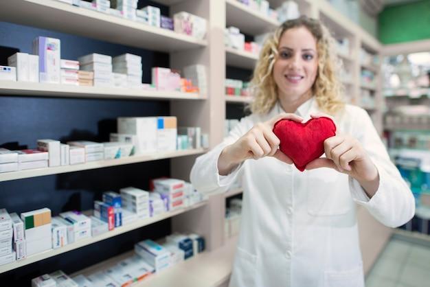 Farmacêutica feminina segurando coração e promovendo medicamentos cardiovasculares e tratamento bem-sucedido Foto gratuita