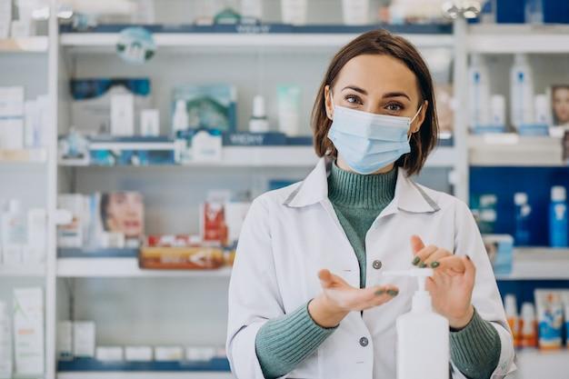 Farmacêutica jovem desinfetando mãos com sanitazer Foto gratuita