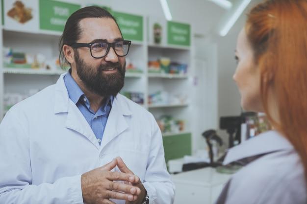 Farmacêutico barbudo alegre bonito falando com um cliente na farmácia Foto Premium