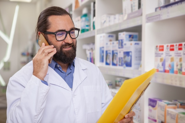 Farmacêutico considerável maduro que atende chamadas, trabalhando na farmácia Foto Premium