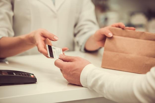 Farmacêutico dando uma compra para um cliente e falando. Foto Premium