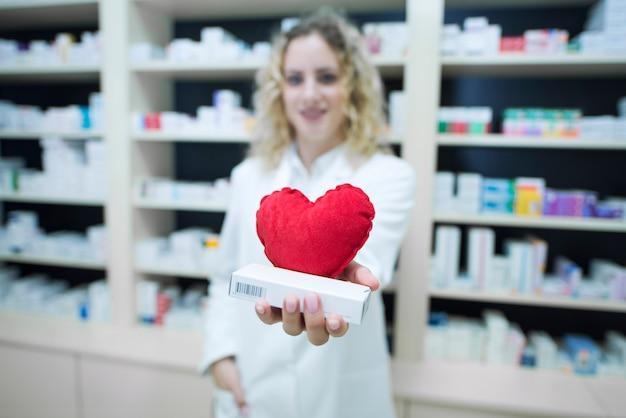 Farmacêutico de uniforme branco segurando medicamentos para doenças cardiovasculares Foto gratuita