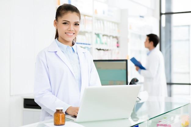 Farmacêutico feminino asiático sorridente, trabalhando na farmácia Foto Premium