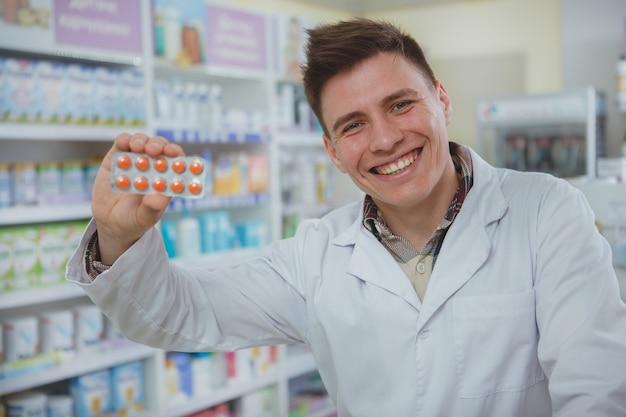 Farmacêutico masculino bonito, trabalhando em sua farmácia Foto Premium