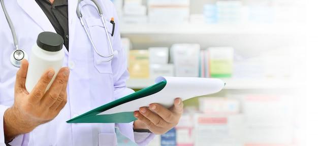 Farmacêutico, segurando o frasco de medicamento e tablet computador para preenchimento de prescrição em farmácia farmácia Foto Premium