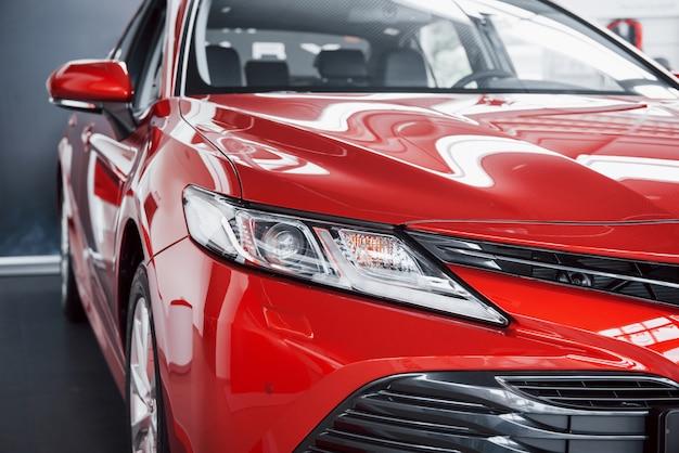Faróis do novo carro vermelho, na concessionária. Foto gratuita