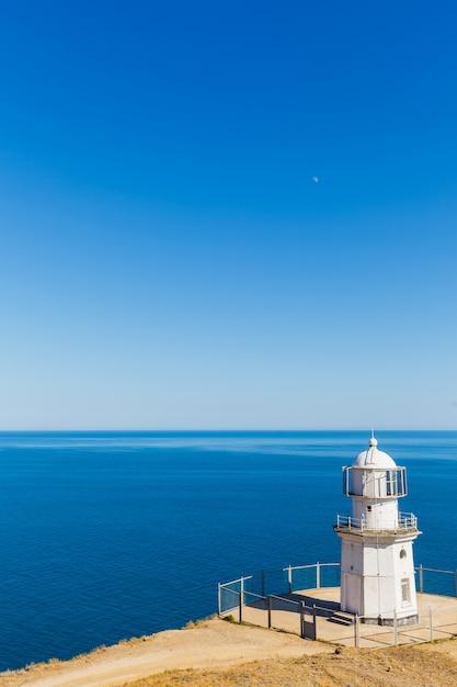 Farol branco em um fundo de mar azul Foto Premium