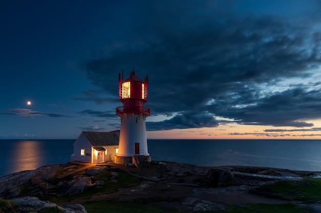 Farol com pedras à noite, farol com luzes acesas ao pôr do sol Foto Premium