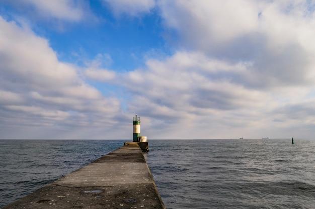 Farol em um píer no mar, um símbolo de esperança Foto Premium