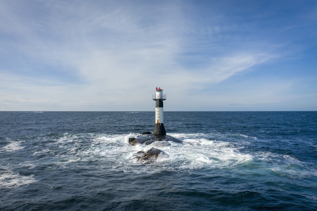 Farol no meio do mar sob o céu nublado Foto gratuita