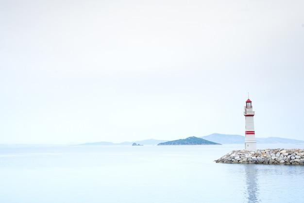 Farol solitário em uma estrada de pedra no meio do mar, com vista para as montanhas e nevoeiro Foto Premium