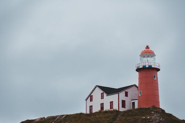 Farol vermelho ao lado da casa Foto gratuita