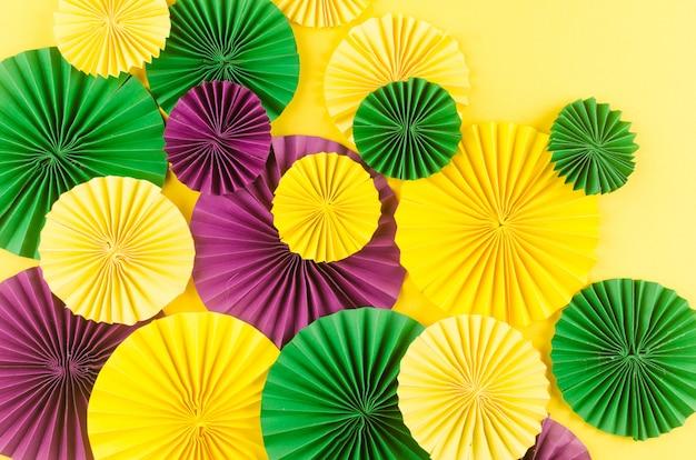 Fãs de carnaval colorido na mesa amarela Foto Premium