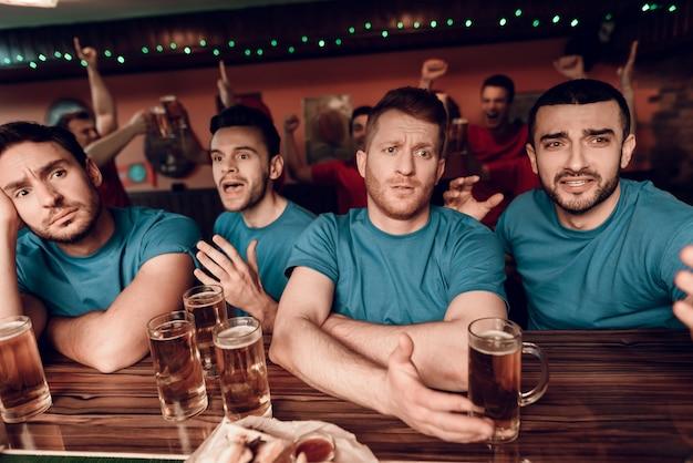 Fãs de equipe azul triste no bar no bar de esportes Foto Premium
