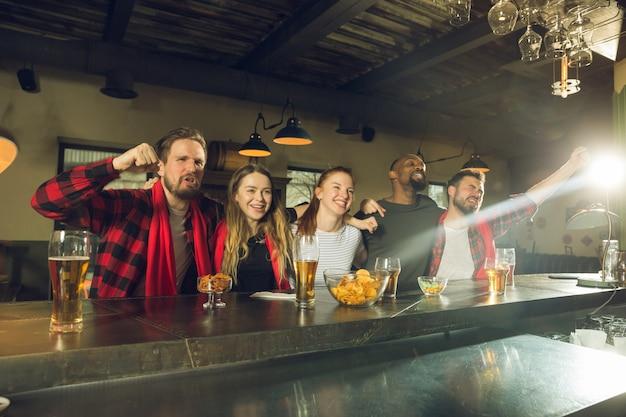 Fãs do esporte torcendo no bar, pub e bebendo cerveja durante o campeonato, a competição vai Foto gratuita