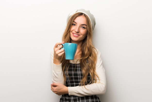 Fashionably mulher usando chapéu segurando uma xícara de café quente Foto Premium